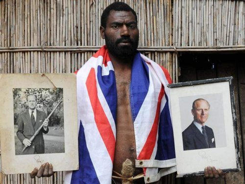 Sikor Natuan, the son of the local chief, holds two official portraits Prince Philip in front of the chief's hut in the remote village of Yaohnanen on Tanna in Vanuatu. This image was taken ahead of the Duke's 90th birthday.