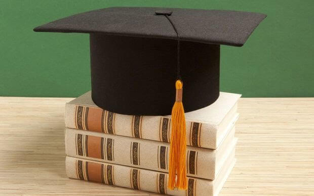 A mortarboard sitting on top of a stack of books